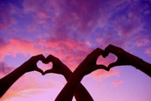 A couple's hands make heart shapes while held up to a beautiful sunset sky