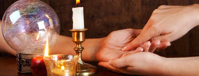 A reader doing palm readings next to candles and a crystal ball
