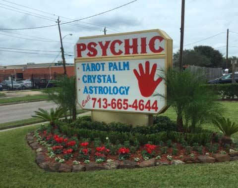 Psychic Elaine Palmer Location Sign found in a nice flower bed in front of location